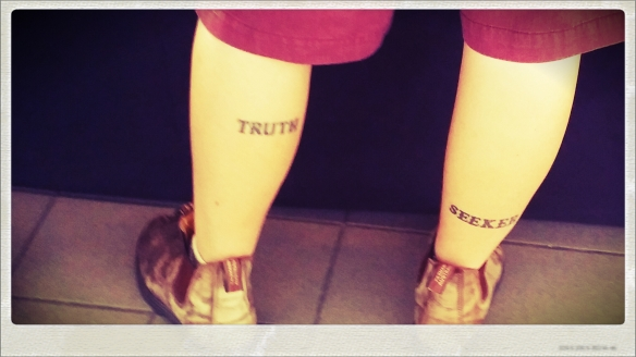 A picture of legs with Truth Seeker tattooed on them